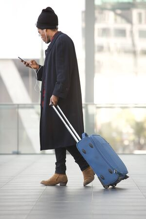 Full body side portrait of african american travel man walking with mobile phone and suitcase at station