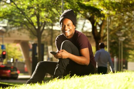 Portrait of happy handsome young black man sitting in park with mobile phone