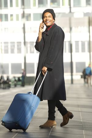 Full length portrait of smiling african american travel man walking in station with mobile phone and suitcase