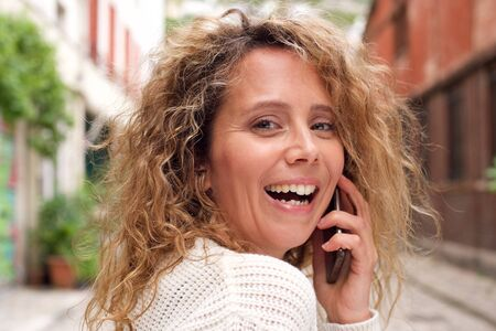 Close up portrait of happy middle age woman talking with cellphone Stock Photo