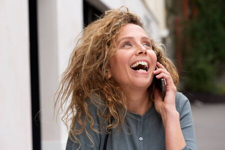 Close up portrait of attractive middle age woman laughing while talking with cellphone 스톡 콘텐츠