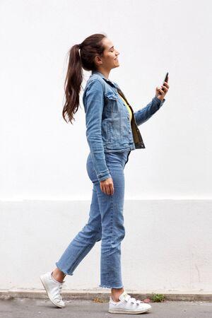Portrait de toute la longueur d'une jeune femme aux cheveux bruns marchant et regardant un téléphone portable par un mur blanc