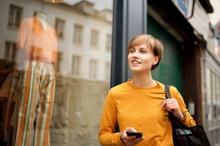 Portrait of young woman walking in city with mobile phone and bag