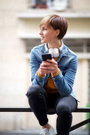 Portrait of cool young woman sitting with headphones and smart phone
