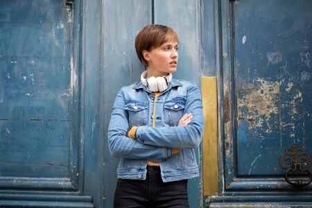 Portrait of cool young woman standing outside with arms crossed by blue door Banque d'images