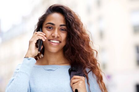 Close up front portrait of attractive young Indian woman smiling and talking with cellphone Stockfoto