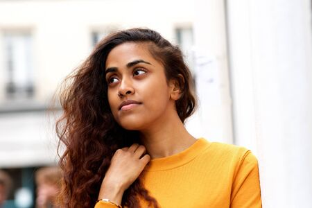 Close up portrait of beautiful young indian woman with piercing looking away