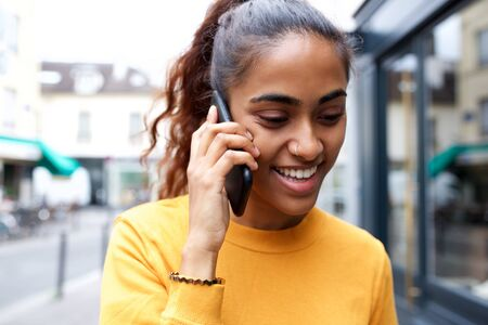 Close up portrait of happy young woman talking with smart phone in city Stock Photo
