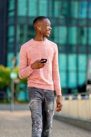 portrait young black man walking with mobile phone and earphones in city