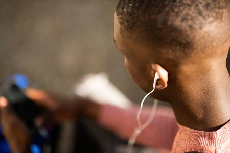 Close up portrait of african american man listening ti music with earphones