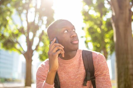 Close up portrait of african american man talking with mobile phone outside