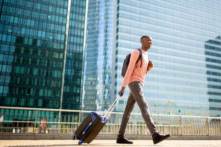 Full length side portrait of young black man walking with suitcase in city