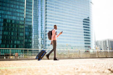 Full body side portrait of young black man walking with phone and suitcase in city Reklamní fotografie - 130816815