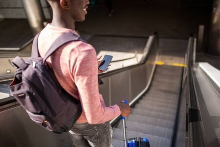 Portrait from behind of young black man going down escalator with mobile phone and suitcase