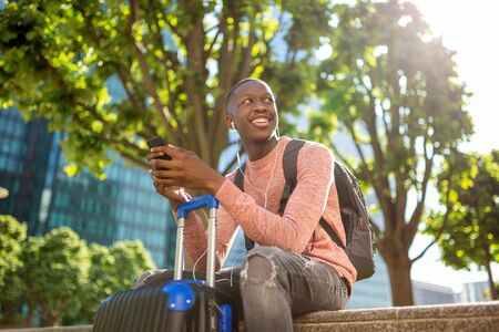 Portrait of young black man smiling with mobile phone and travel bags