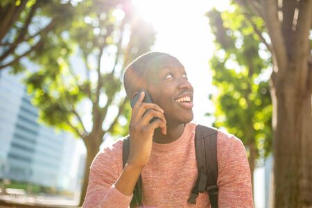 Portrait of smiling young african american man talking with mobile phone ion city park Reklamní fotografie