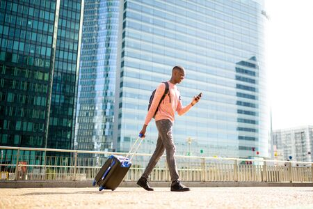 Full body side portrait of young black man walking with mobile phone and suitcase in city Фото со стока