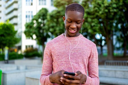 Portrait of smiling young black man listening to music with MP3 player mobile phone Banco de Imagens