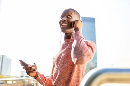 Portrait of laughing young black man with mobile phone and earphones Фото со стока