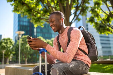 Portrait of happy young black man sitting with bags and looking at mobile phone