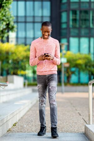Full length portrait happy young black man walking with mobile phone and earphones Banco de Imagens