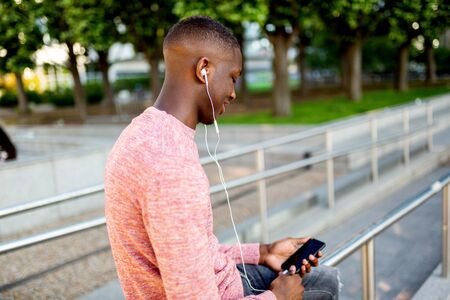 Side portrait of young african american man listening to music with headphones and mobile phone