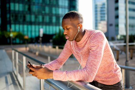 Side portrait of cool young black guy listening to music with headphones and mobile phone