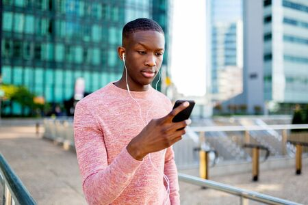 Portrait of young black man listening to music with headphones and phone in the city