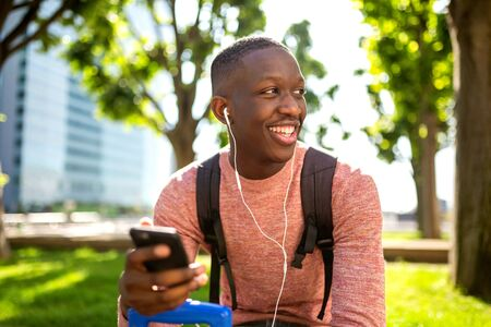 Portrait of happy young black man listening to music with mobile phone and earphones Фото со стока