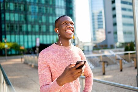 Portrait of happy young black man laughing and listening to music with mobile phone and earphones in the city