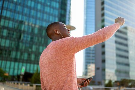 Portrait of happy young black man punching the air while listening with mobile phone and earphones