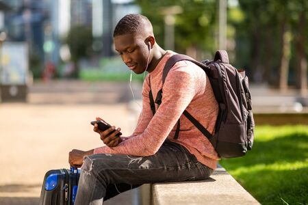 Portrait of young black travel man sitting outside with mobile phone and bags