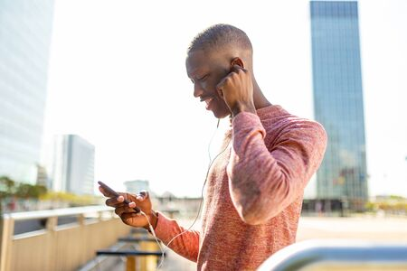 Side portrait of african man looking at cellphone while listening to music Banco de Imagens