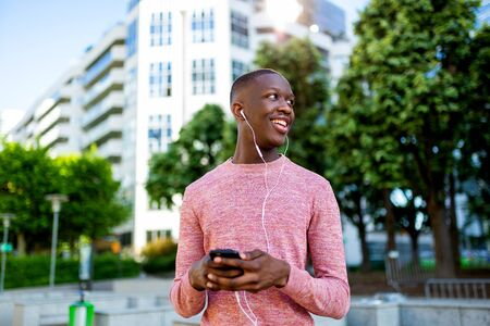 Portrait of smiling young black man listening to music with  mobile phone and headphones