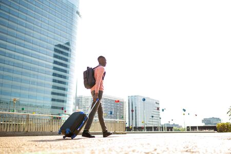Full length portrait of young black man walking with suitcase in city