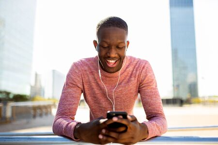 Portrait of happy young black man listening to music with phone and earphones in urban landscape