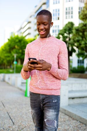 Portrait of happy young african man listening to music with mobile phone and headphones
