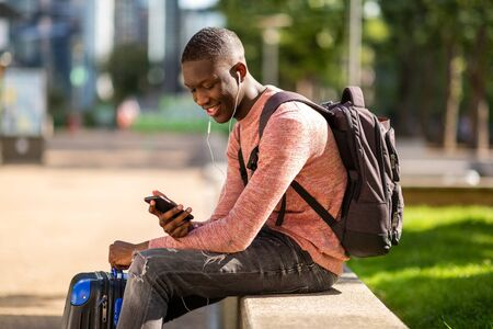Side portrait of young african man sitting outside with travel bags and mobile phone Фото со стока