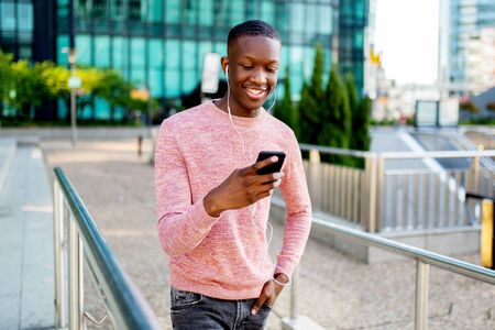 Portrait of happy young black man listening to music with phone and earphones while walking in city