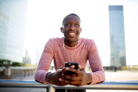 Portrait of smiling young black guy listening to music with earphones and mobile phone Banco de Imagens