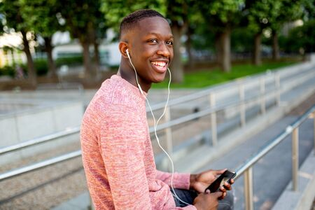 Portrait of smiling young african american man listening to music with headphones and mobile phone