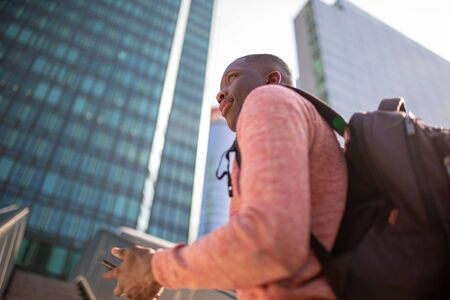 Portrait from side of young black man with mobile phone and bag in city 版權商用圖片 - 130816901
