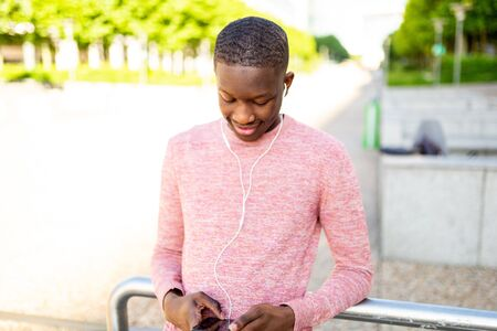 Portrait of young black man smiling and listening to music with headphones and mobile phone