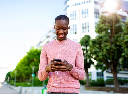 Portrait of happy young african man listening to music with phone and headphones
