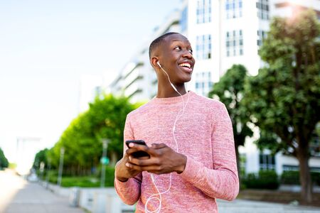 Portrait of smiling young black man listening to music with  phone and headphones