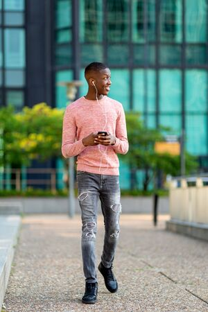 Full length portrait young black man walking with mobile phone and earphones