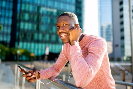 Portrait of smiling young black man listening to music with headphones and cellphone in the city