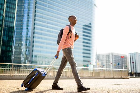 Full body side portrait of young black man walking with suitcase in city