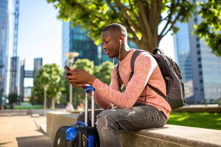 Portrait of young travel man sitting outside with mobile phone and suitcase Reklamní fotografie