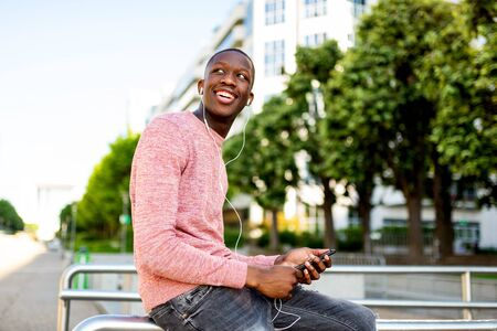 Side portrait of happy young black man listening to music with headphones and mobile phone